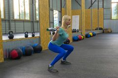 Blonde girl makes a squats holding a barbell without weight on t stock photos