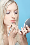 Blonde girl making up. Portrait of beautiful slavonic blonde girl making up on blue royalty free stock photography