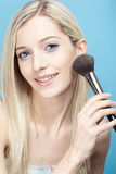 Blonde girl making up Stock Images