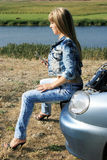 Blonde girl-mechanic sitting on the car Royalty Free Stock Photo