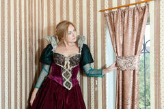 Blonde girl in medieval dress window Royalty Free Stock Images