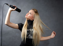 blonde girl with microphone Royalty Free Stock Image