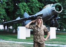 Blonde girl in military uniform staying near the big plane looking at camera royalty free stock photo
