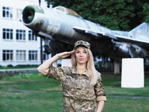 Blonde girl in military uniform staying near the plane looking at camera stock image