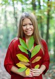 Blonde girl in a misterious forest holding a branch with autumn Stock Image