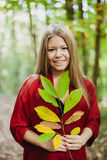 Blonde girl in a misterious forest holding a branch Royalty Free Stock Photography