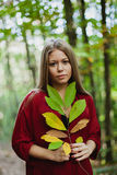 Blonde girl in a misterious forest holding a branch Royalty Free Stock Photo