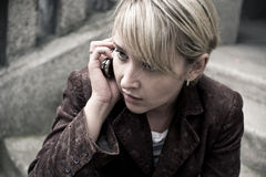 Blonde girl with mobile phone. Young blonde girl with fringe, dressed in velvet brown jacket, is talking on the phone, looking sideways Stock Photo