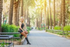 Blonde girl model in black posing outdoors. In sunny day Royalty Free Stock Photo