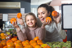 Blonde girl with mother buying mandarins in shop Stock Photography