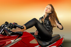 Blonde girl on a motorcycle. Pretty blonde woman on a big red motorcycle Stock Photography