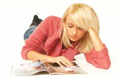 Blonde girl with newspaper. Close up royalty free stock photography
