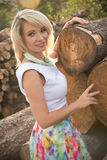Blonde girl next to logs in sunset Royalty Free Stock Photography
