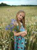 Blonde girl with nosegay. Blonde girl on background of landscape of cereal field with blue cornflower and camomille stock image