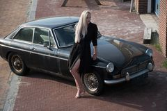 Blonde girl and old black car stock image