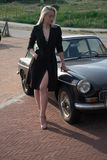 Blonde girl and old black car royalty free stock image