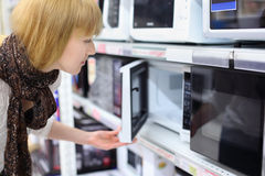 Blonde girl opens microwave in shop Royalty Free Stock Photography