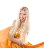 Blonde girl in orange flying dress Royalty Free Stock Images