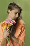 Blonde girl with in orange holding flowers, Stock Photos