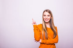 Blonde girl in orange t-shirt pointed with finger up on white. Happy blonde girl in orange t-shirt pointed with finger up on white royalty free stock photos