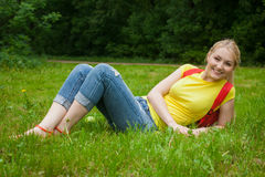 Blonde girl out in the open air wearing jeans and bag Royalty Free Stock Photography