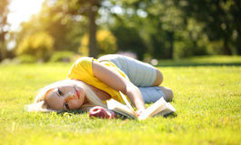 Blonde Girl Outdoor. Beautiful Woman with Book and Apple Royalty Free Stock Photo