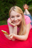Blonde girl outdoor in the park using her cell phone Stock Image