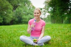 Blonde girl outdoor in the park with water and apple Royalty Free Stock Image