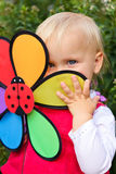 Blonde girl outdoors. Portrait of cute little girl hiding behind flower toy outdoors Stock Photography