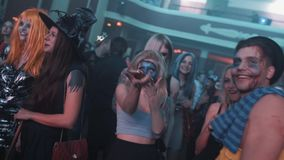 Blonde girl with painted face dance in crowd at halloween night club party. Blonde girl with painted face and guy in zombie makeover dance in crowd at halloween stock video footage
