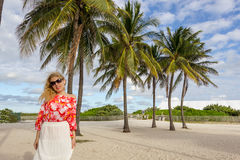 Blonde girl with palm trees in sands of the beach Royalty Free Stock Photos