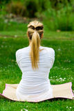 Blonde girl in park doing yoga Royalty Free Stock Photography