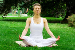 Blonde girl in park doing yoga Royalty Free Stock Images