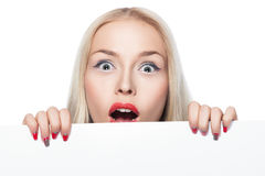 Blonde girl peeking out from behind the poster. Stock Photography