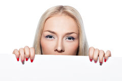 Blonde girl peeking out from behind the poster. Stock Images