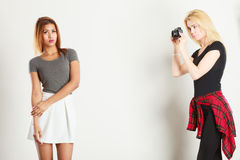 Blonde girl photographing mulatto woman. Photographer and model. Blonde girl shooting images, taking photos with camera, photographing mulatto female model Stock Image