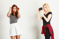 Blonde girl photographing mulatto woman. Photographer and model. Blonde girl shooting images, taking photos with camera, photographing mulatto female model Royalty Free Stock Photos