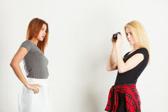 Blonde girl photographing mulatto woman. Photographer and model. Blonde girl shooting images, taking photos with camera, photographing mulatto female model Stock Photos