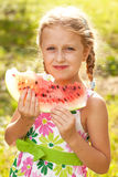 Blonde girl with pigtails eating a watermelon Royalty Free Stock Photo