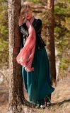 Blonde girl in a pine forest stock image