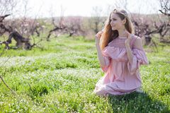 Blonde girl in pink dress is collecting flowers in the garden. 1 stock images
