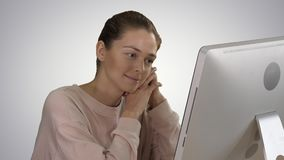 Blonde girl with pink pullover looking at monitor of computer watching video on gradient background. Close up. Blonde girl with pink pullover looking at monitor stock footage