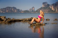 Blonde girl in  pink swimsuit sits on stone Royalty Free Stock Images