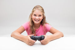 Blonde girl in pink is a videogame player. Girl grinning with a gamepad or video game controller - concept of videogame player Royalty Free Stock Images