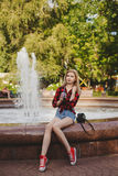 Blonde girl in a Plaid Shirt at the fountain royalty free stock photography