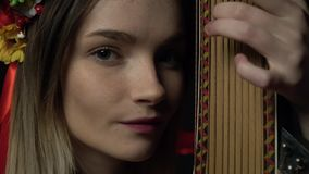 A blonde girl plays on a bandura and looks gently into the camera. The gray-eyed blonde plays a traditional bandura instrument stock video