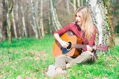 Blonde girl plays guitar stock photos