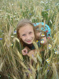 Blonde girl plays hide and seek in field flowers Royalty Free Stock Photos