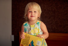 Blonde girl plays with large colorful childish book Stock Photography
