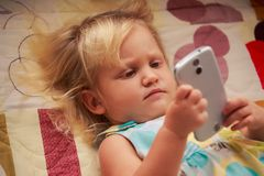 blonde girl plays with smartphone Stock Photos
